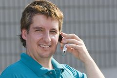 Man with cell phone. Man in late thirties with blue shirt talking on a cell phone Stock Photo