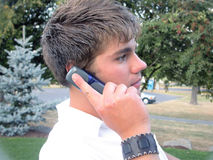 Man on Cell Phone. A young man looks at the camera while talking on his cell phone royalty free stock images
