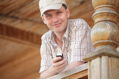 Man with cell phone. On the wooden porch Stock Photo