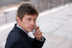 Man with cell phone. Man using cell phone outside building, looking back Stock Image