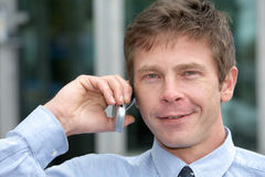 Man with cell phone. Man using cell phone outdoors, smiling, close-up Royalty Free Stock Images