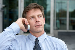 Man with cell phone. Man using cell phone outdoors, looking up Stock Image