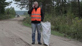 Man with cell phone and bag of plastic bottles on the road in forest. In summer day stock footage