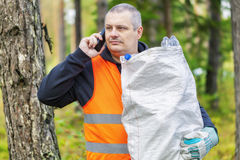 Man with cell phone and bag of plastic bottles Stock Photos