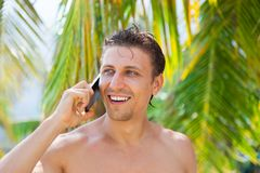 Man cell phone call smile on beach summer vacation. Green leaves palm tree background tourist ocean travel communication Stock Photo