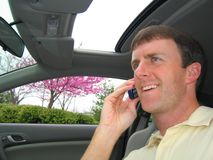 Man on Cell Phone in Car. A man driving a car and smiling while talking on his cell phone Royalty Free Stock Photography