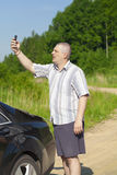 Man with the cell phone on the country road Royalty Free Stock Images