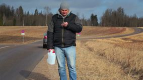 Man with cell phone and empty can waiting for help near car stock video footage