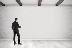 Man with cell phone in empty room. Rear view of businessman with cellphone looking at concrete wall in empty room. 3d rendering. Mockup Stock Images
