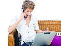 Man on cell phone in front of laptop Royalty Free Stock Photo