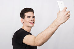 Man with cell phone. Handsome man taking a selfie with mobile phone Stock Photography