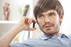 Man with cell phone at home. Young man speaking on cell home while sitting on sofa at home Royalty Free Stock Image