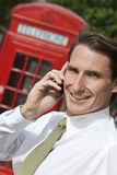 Man on Cell Phone In London With Red Telephone Box. A successful businessman talking on his cell phone in London, England, with a classic red telephone box out Stock Photos
