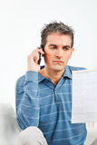 Man with cell phone and phone bill. In living room Royalty Free Stock Photo