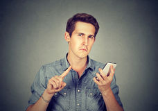 Man with cell phone showing no, don't, attention with finger gesture Royalty Free Stock Image