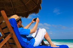 Man with cell phone on tropical beach Royalty Free Stock Photography