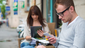 Man with cell phone and the woman with the iPad sitting in a café.