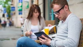 Man with cell phone and the woman with notes sitting in a café. Stock Images