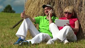 Man with cell phone and woman with Tablet PC sits near a haystack stock video
