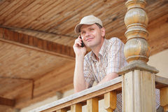 Man with cell phone. On a wooden porch Royalty Free Stock Photos