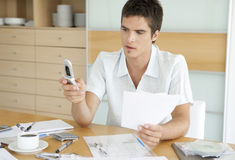 Man With Cell Working on Finances. Man using his cell phone while working on finances in his home's kitchen Royalty Free Stock Photo