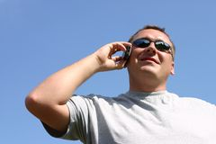 Man on the cellphone. Smiling man talking, blue sky as a background Royalty Free Stock Image
