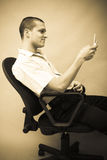 Man with cellphone. An attractive caucasian white man profile with smiling facial expression using his cellphone while sitting on a chair. Image in sepia stock photos