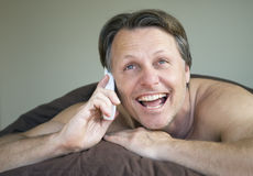 Man on cellphone. A forties man enjoys a friendly chat on his cellphone while laying bed Royalty Free Stock Photo