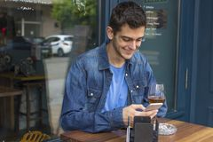Man with the cellphone in the bar. Young man with the cellphone in the bar Stock Photography