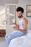 Man cellphone coffee bed Royalty Free Stock Image