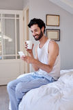 Man cellphone coffee bed Stock Photo