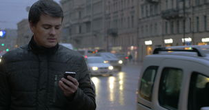Man with cellphone in the evening rainy city stock video footage