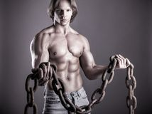 Man with a chain. Close up of a healthy strong man with chain in hands on a gray background Stock Photo
