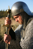 Man in chain mail kneeling and gripping a sword