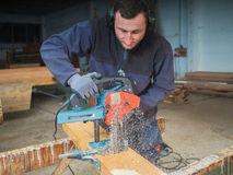 Man with chain mortiser mill-cuts a wooden board Royalty Free Stock Photos