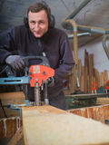 Man with chain mortiser mill-cuts a wooden board Royalty Free Stock Image