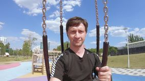 The man on the chain swing. In the children`s park, an adult man rides a chain swing stock footage