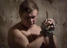 Man with a chain tied hands Stock Photos