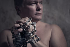 Man with a chain tied hands Stock Photo