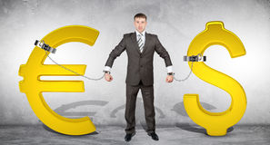 Man chained with golden dollar and euro signs Royalty Free Stock Images