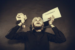 Man with chained hands holding contract and money Royalty Free Stock Photo