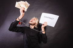 Man with chained hands holding contract and money Royalty Free Stock Photography