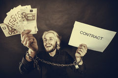 Man with chained hands holding contract and money. Stress at work, no freedom, pursuit of money concept. Mad man with chained hands holding money and contract Royalty Free Stock Photos