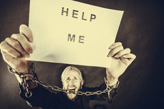 Man with chained hands holding help me sign Stock Image