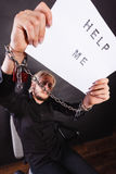 Man with chained hands holding help me sign Royalty Free Stock Photography