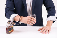 Man chained to alcoholic beverage Stock Photo