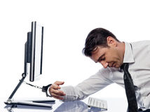 Man chained to computer with handcuffs sad royalty free stock photo