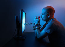Man chained to computer. A man is chained to computer late at night royalty free stock photos