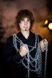 Man chained. Young handsome man boy model actor hostage slave captive. Art makeup paint black gray temple chin long hair. Hands chained desire call to action Royalty Free Stock Images