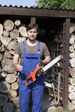 Man with chainsaw. Looking into the camera and thumb up stock photography